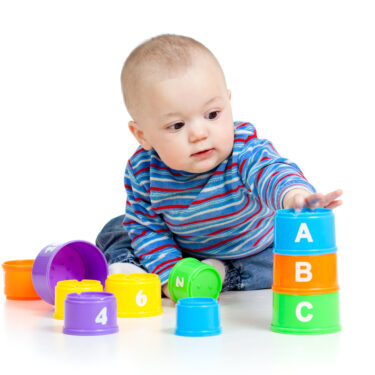 Baby sitting up playing with colorful educational blocks
