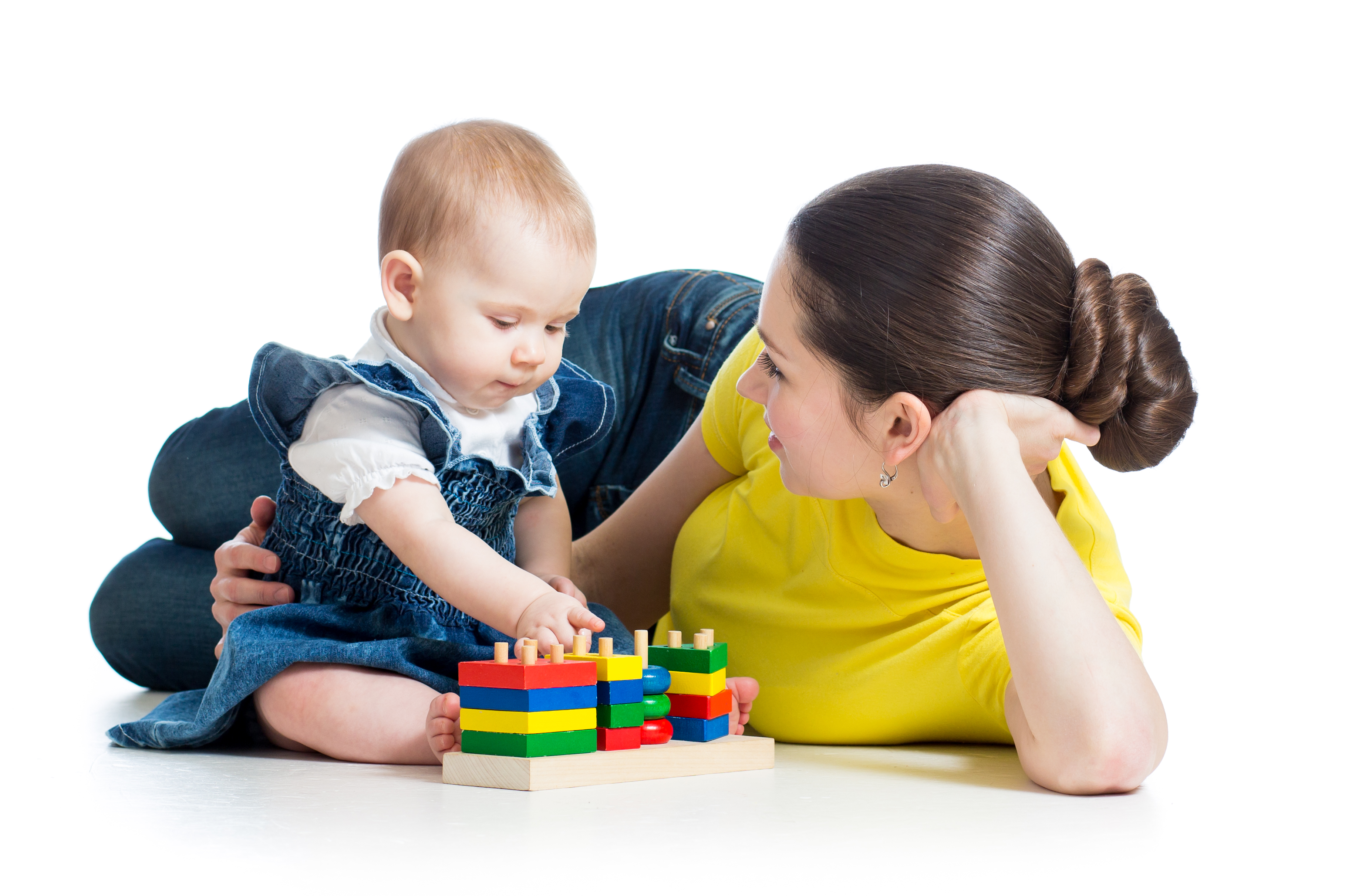 Mother propped up on elbow beside baby daughter who is playing with blocks