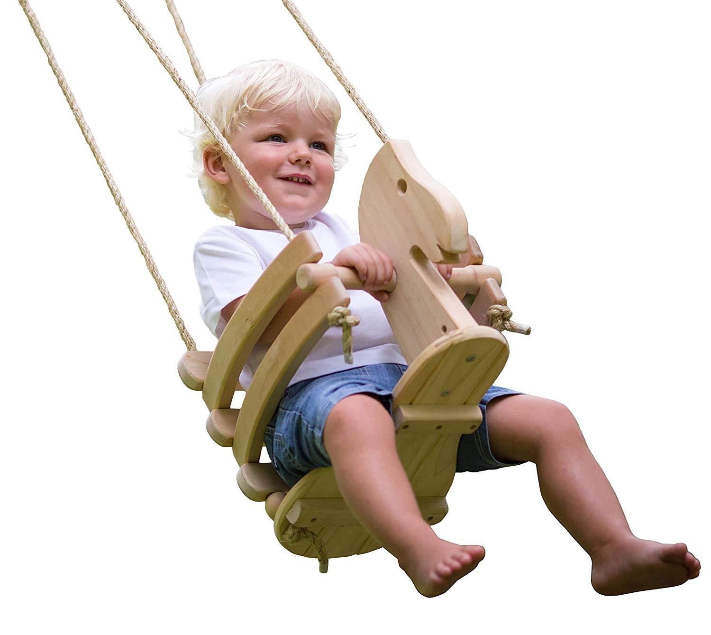 Toddler boy swinging on wooden horse swing