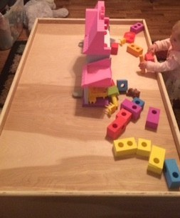 Toddler girl standing next to a play table plaing with colored foam blocks