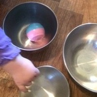 Hand of toddler child playing with steel bowls