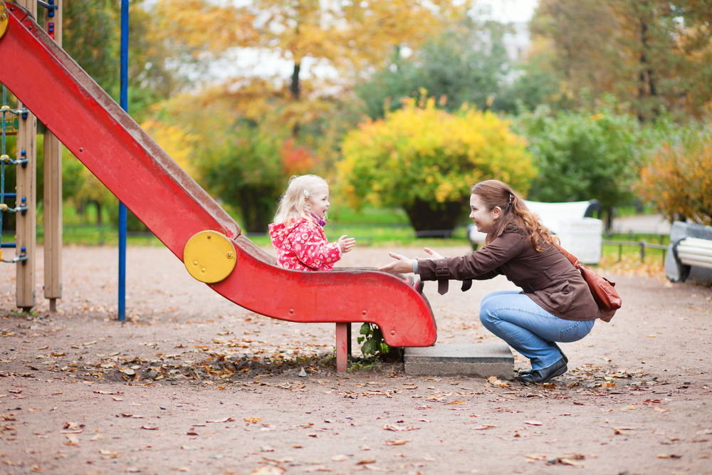 Ways Toddlers Benefit from Slides-Girl sliding down slide to her mother-toyfultykes