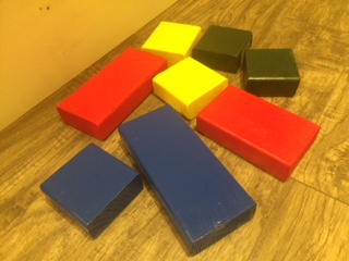 Blue, red, yellow and green wooden blocks on floor