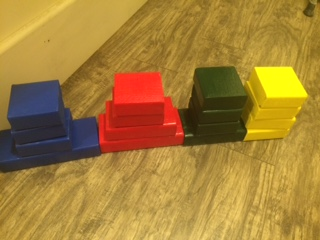 Four sets of four blue, red, green and yellow blocks sorted and stacked by color