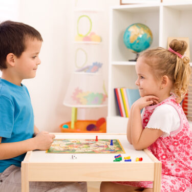 Kids playing board games at small table in their room