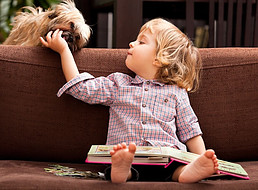 Child with book in lap looking at and petting dog behind him