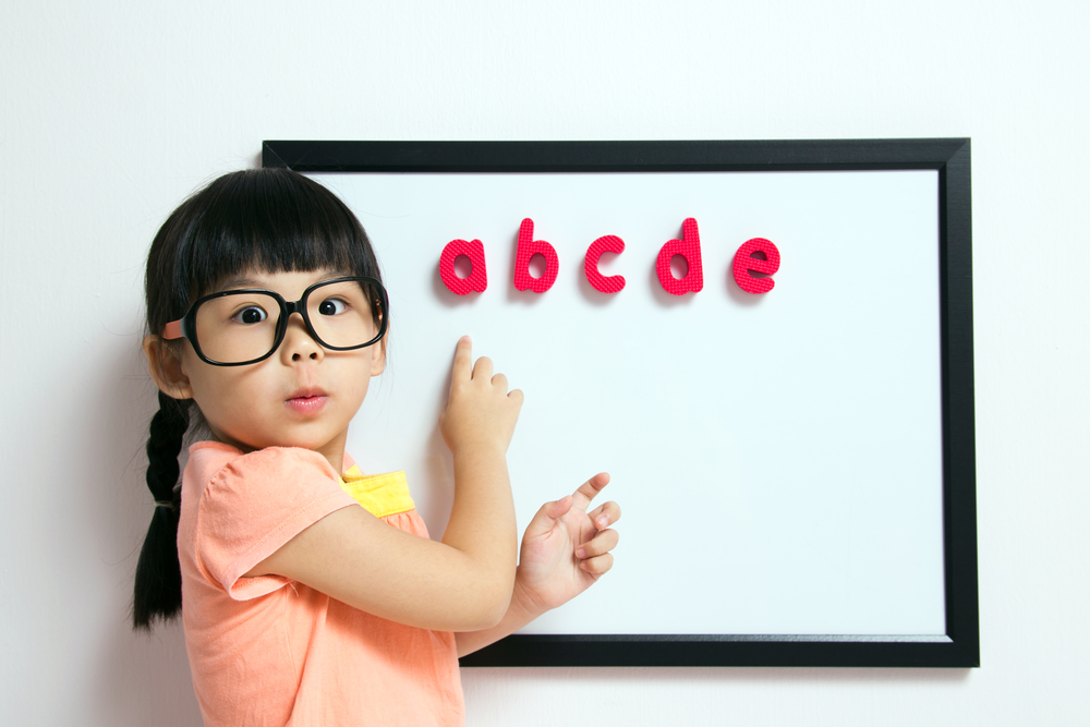 Asian girl putting letters on a magnetic board