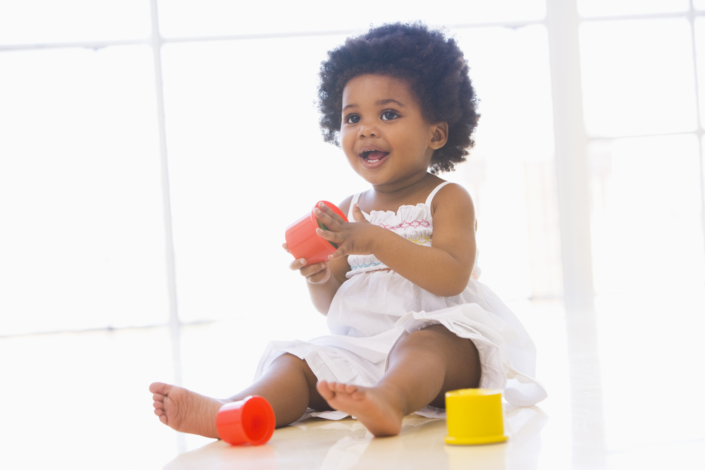 Black toddler girl playing with blocks