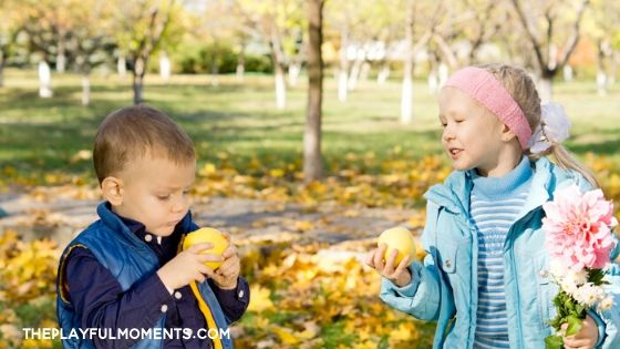 Boy and girl eating yellow apples