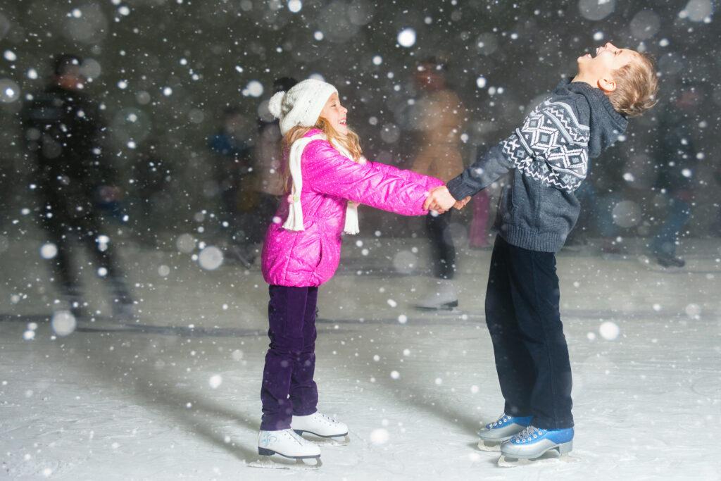 Boy and girl ice skating at night