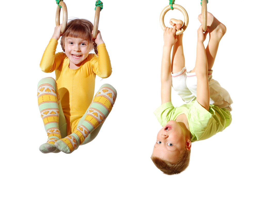 Boy and girl playing on gymnastic rings