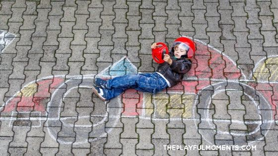 Boy posing for photo by laying on sidewalk chalk drawing
