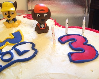 Two Paw Patrol water squirters sitting on top of a birthday cake with a number three on it.