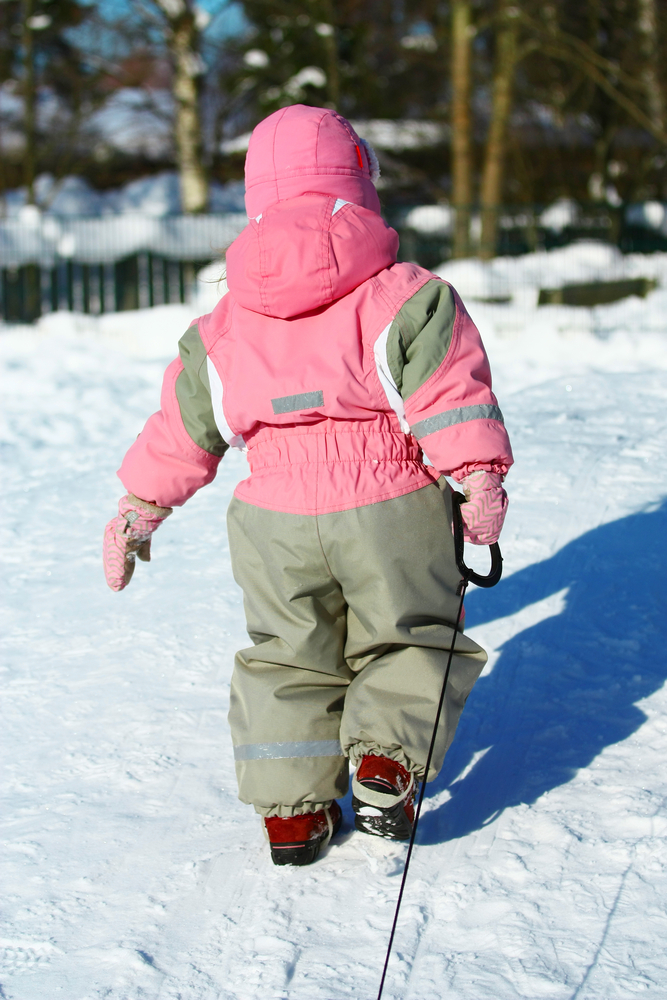 Child in snowsuit pulling sled up hill in the snow