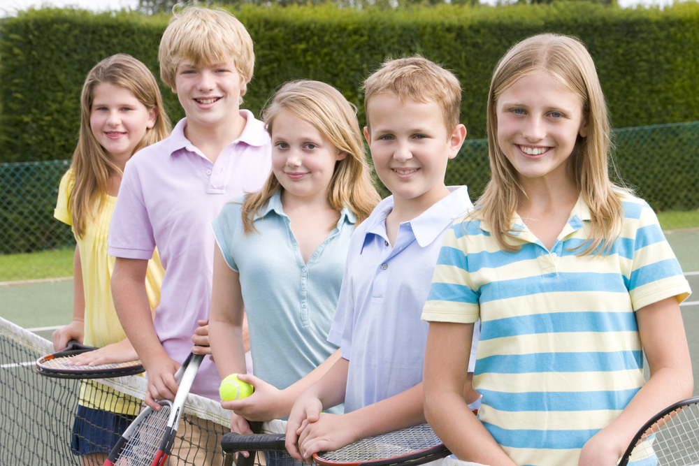 Five kids with rackets standing next to net on tennis court