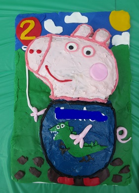 George Pig shaped birthday cake with George holding a balloon with a number 2 on it