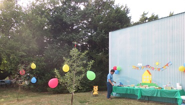 Peppa Pig birthday decorations and balloons set up next to a metal shed outside