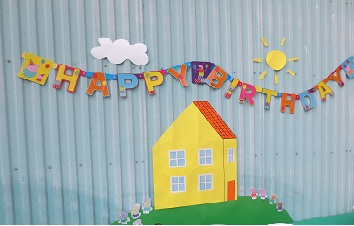 Peppa Pig birthday banner and Peppa's house attaced to outside of shed