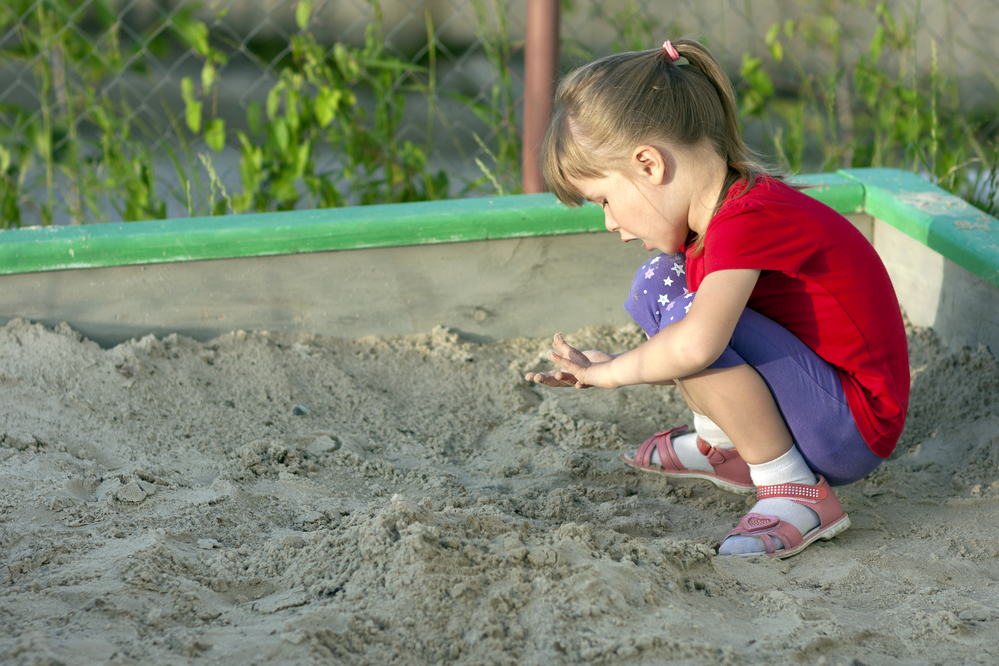 Girl Playing in Sand Box