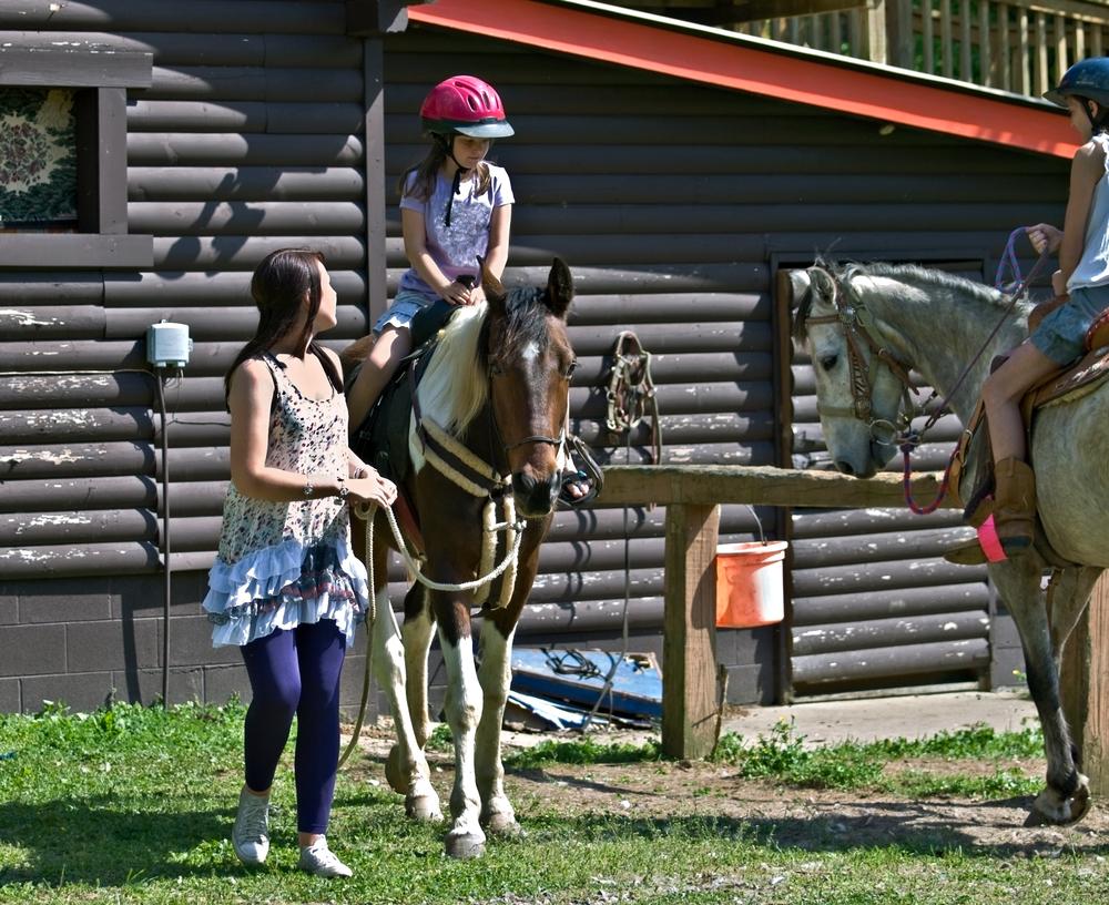 Girl on horseback with lady leading the horse