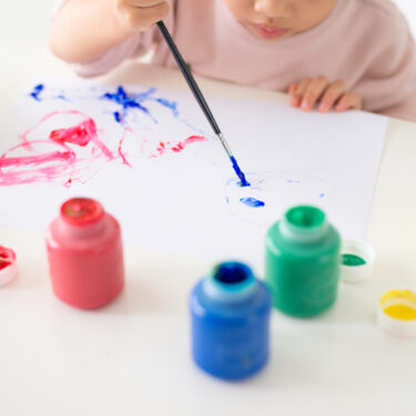 Girl painting with primary colors