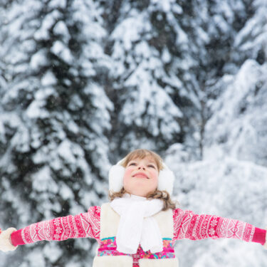 Girl standing in snow with arms outstretched