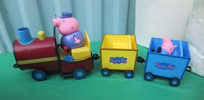 Toy Grandpa Pig driving toy train with toy peppa riding in one of the cars