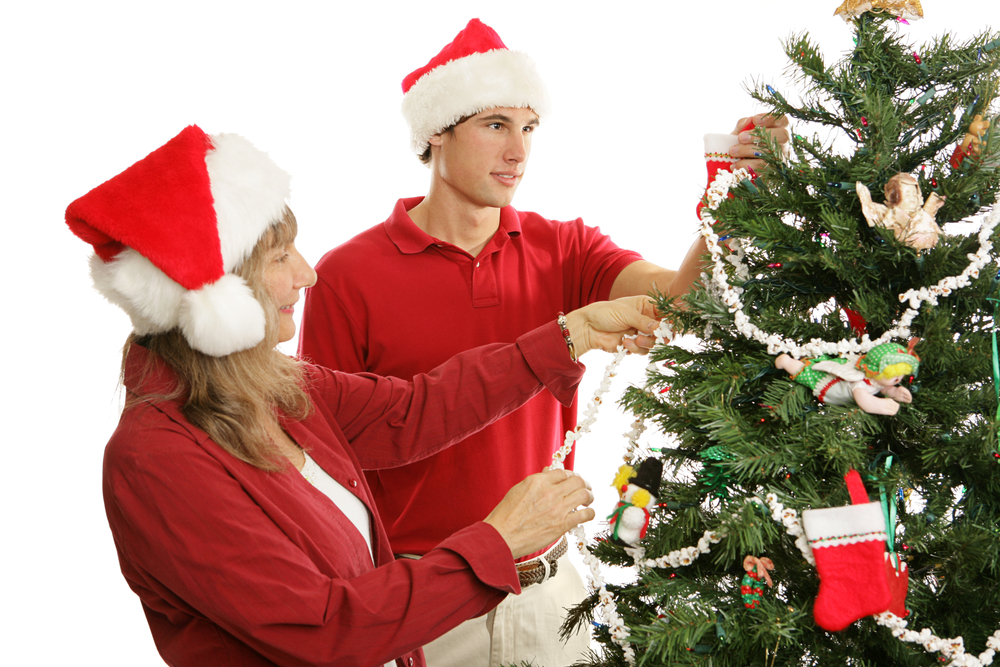 A young man and his mother wearing Santa hats and hanging popcorn garland on a Christmas tree