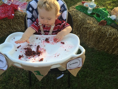 One year old boy sitting in high chair with chocolate birthday cake all over the tray