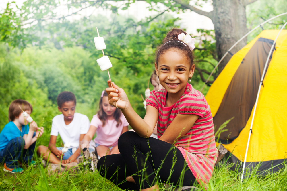 Black girl sitting in front of yellow tent holding a stick with two marshmallows on it with three kids sitting in the background