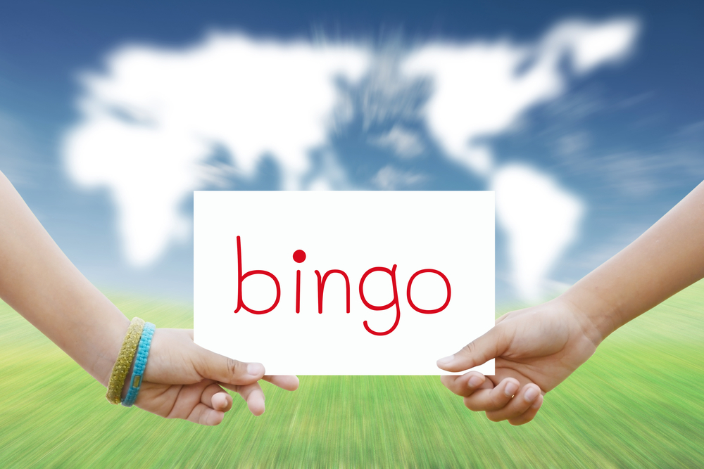 Two hands holding a sign that says bingo
