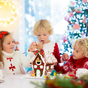 Three kids making a gingerbread house with a Christmas tree in the background