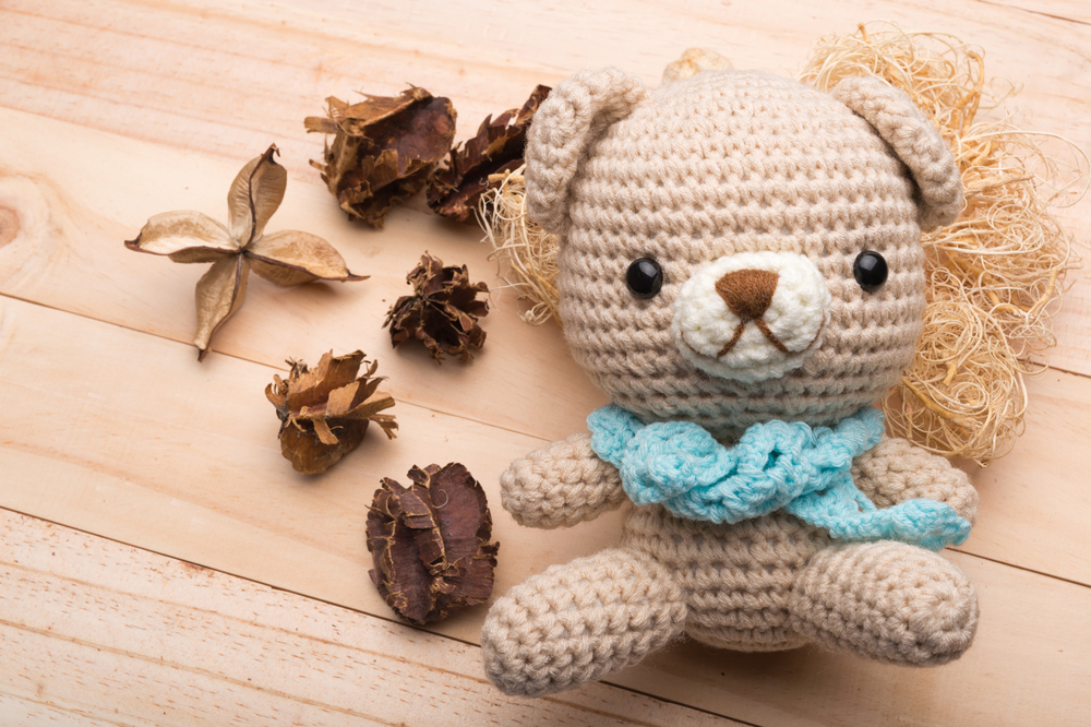 Brown Knitted teddy bear on wood background