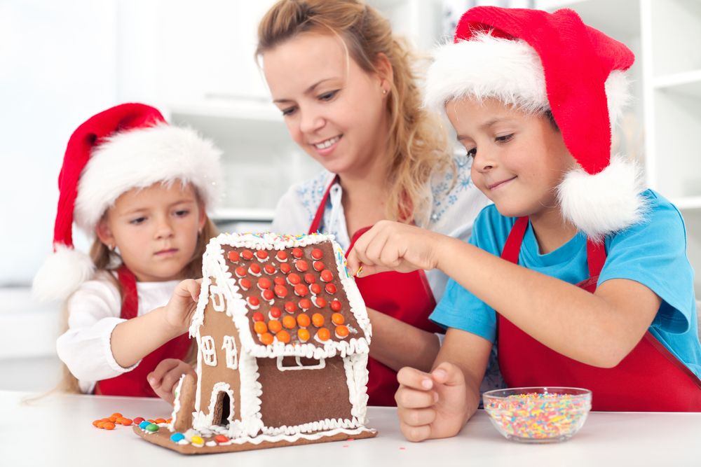 Mom and son and daughter wearing Santa hats decorating a gingerbread house