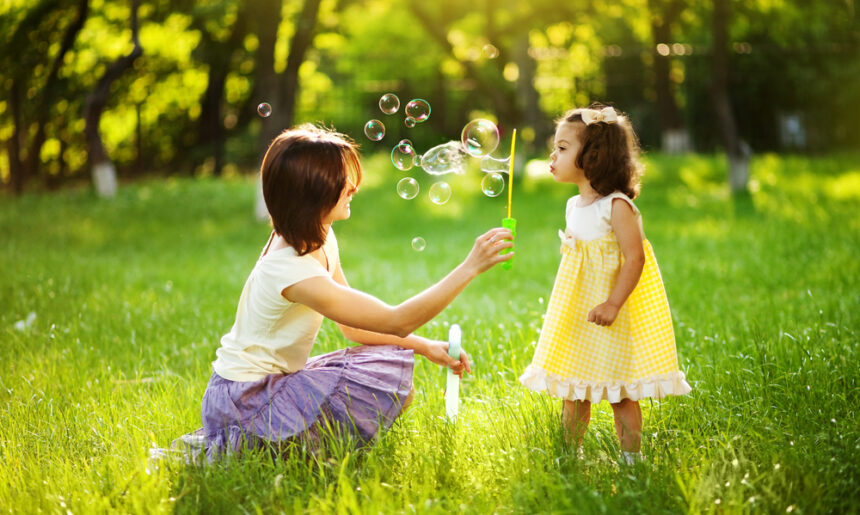 Mother-blowing-bubbles-with-daughter-in-park-theplayfulmoments