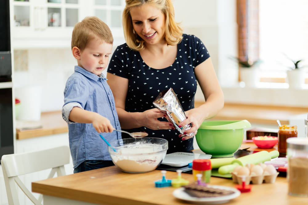 Mom teaching her young son how to bake