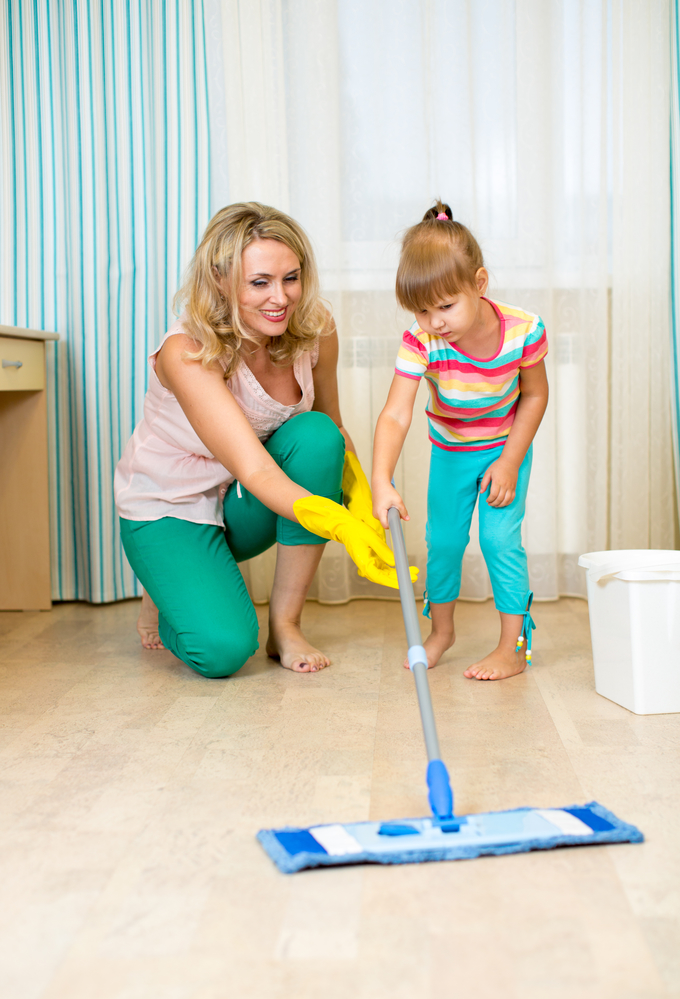 Mom teaching her young daughter how to mop the floor