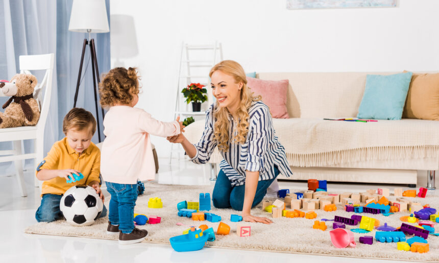 Mom-playing-blocks-with-two-kids-on-living-room-floor-theplayfulmoments