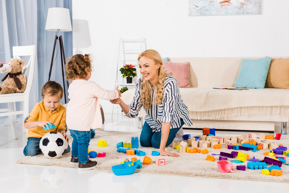 Mom playing in living room with kids