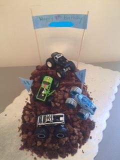 Four toy monster trucks on dirt cake