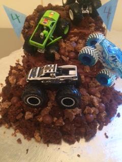 Three toy monster trucks on chocolate cake that looks like dirt