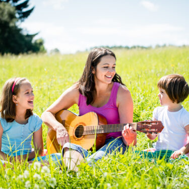Mother Singing Songs With Kids in Meadow