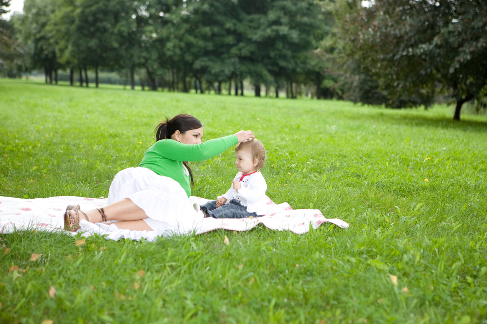 Mother and young child lying on blanket in the grass