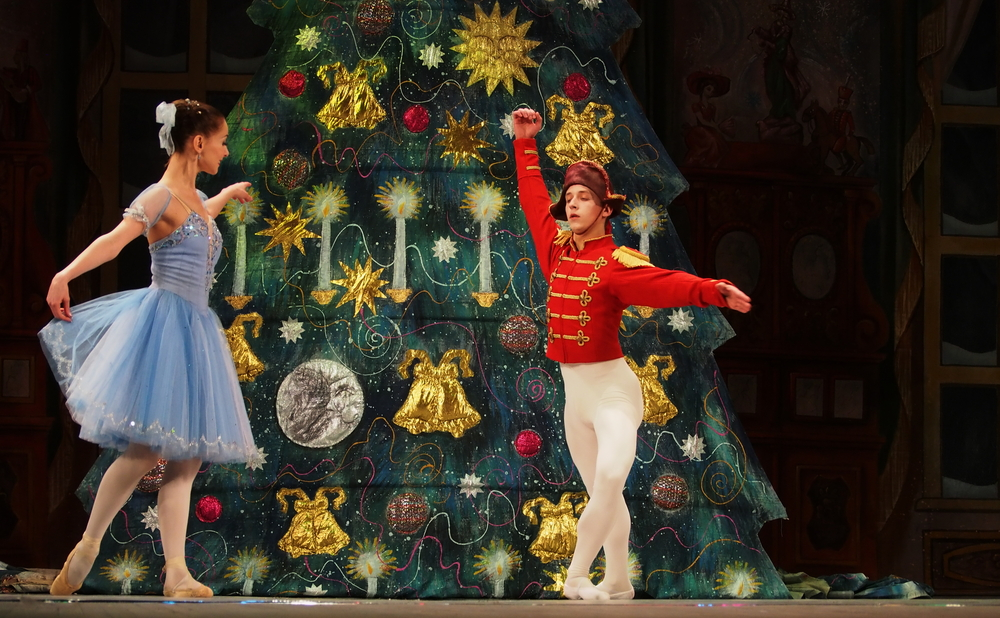 Two Nutcracker Ballet dancers on stage in front of big Christmas tree
