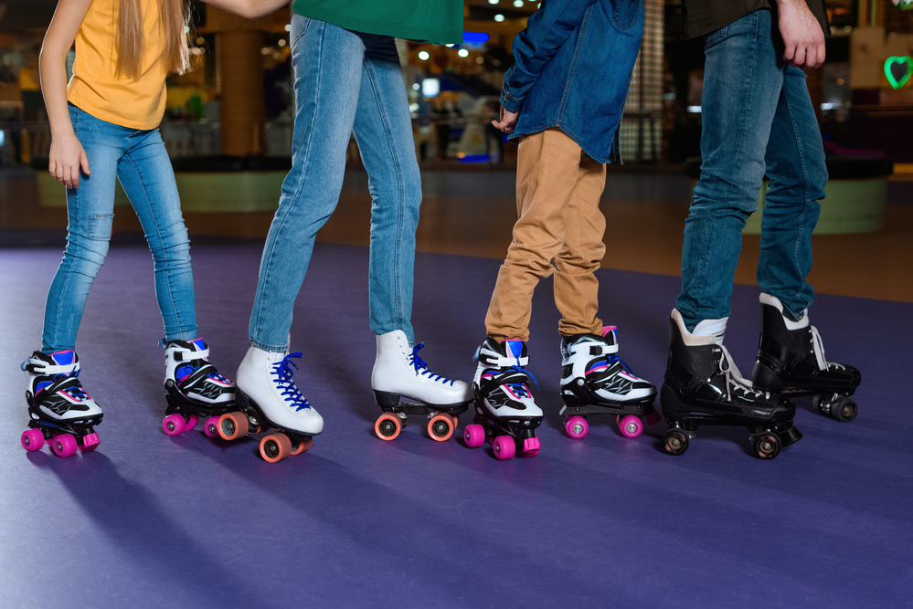 View of legs and feet of parents and kids skating together on roller rink