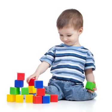 Preschool age boy stacking colorful blocks