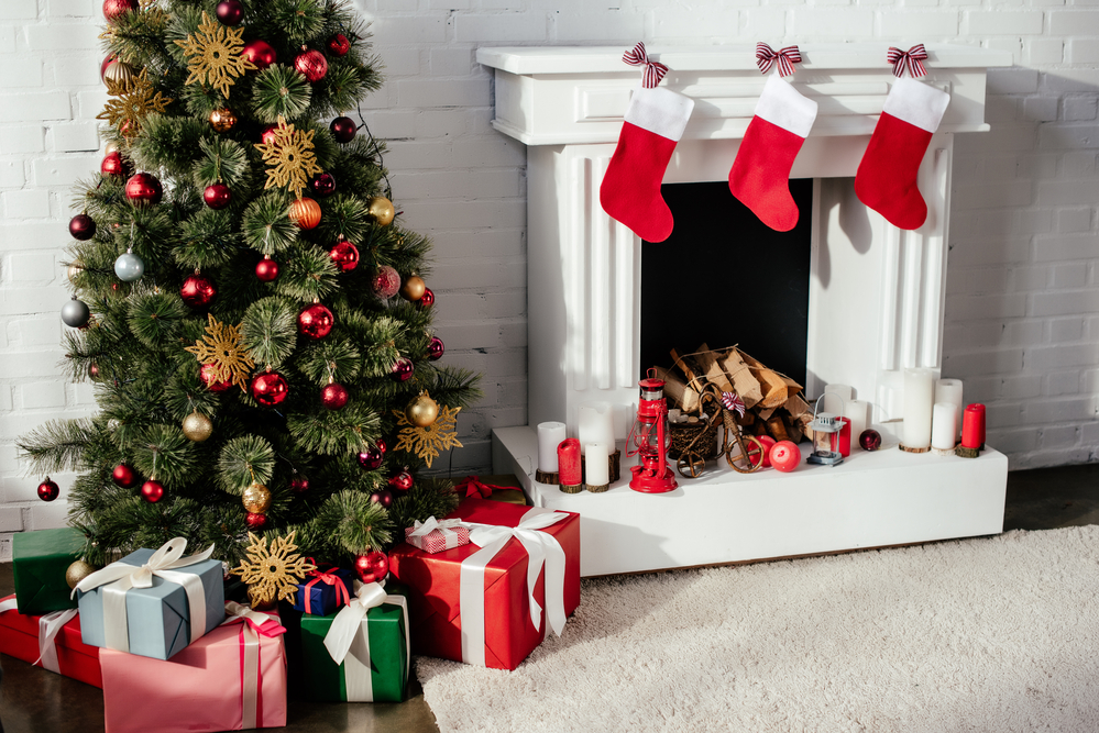 Wrapped presents under a Christmas tree next to a white fireplace with red stockings hung on the mantle