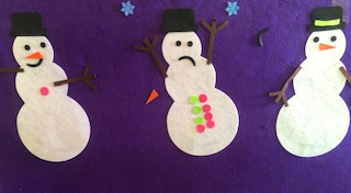 Three snowmen made out of felt on purple background