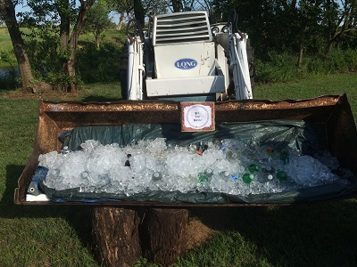 Tractor with bucket scoop filled with crushed ice and soda bottles