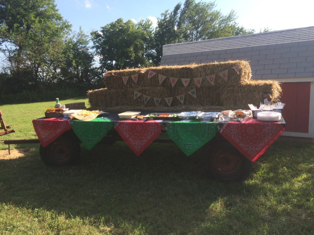 Trailer with hay bales and a happy birthday banner made out of burlap and bandanas